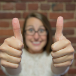 Happy young woman in glasses lifts thumbs upward
