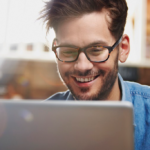 Cheerful businessman in casual clothes and eyeglasses is using a laptop