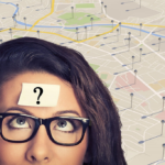 Woman wearing black eyeglasses with a sticky note on her forehead and a map as background