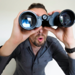 Businessman wearing dark blue sleeves seeking with binocular