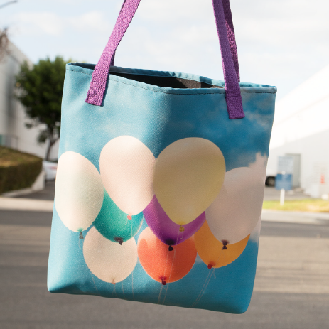 A tote bag with balloons and sky as background print design