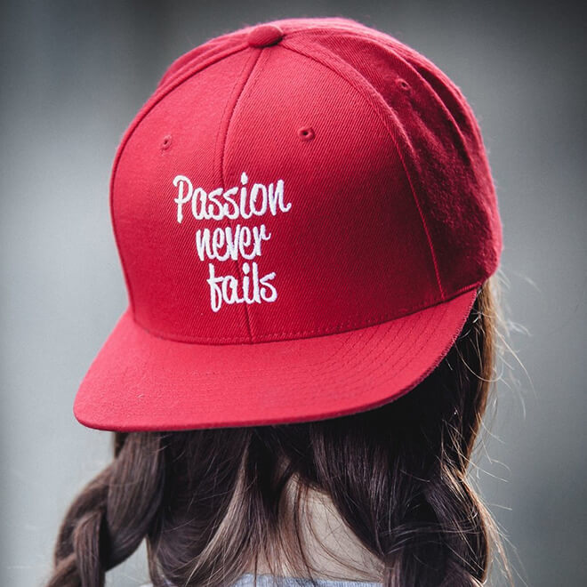 Girl with braided hair wearing a red hat with a white embroidery Passion Never Fails