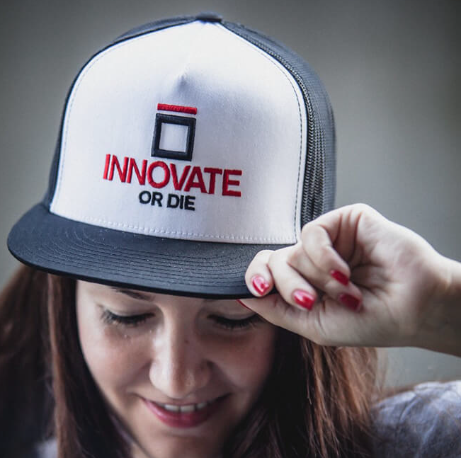 A smiling girl wearing a black and white cap with a red and blue embroidery 'Innovate or Die'