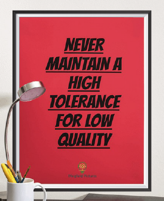 Red poster with black frame with printed quote 'Never Maintain a High Tolerance for Low Quality' hanged on the wall