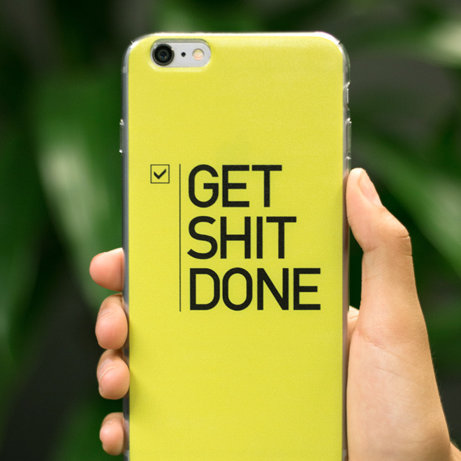 Hand holding a yellow phone case with Get Shit Done print design